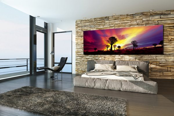Modern sunny bedroom overlooking the ocean with a balcony, view window, contemporary double bed with padded upholstered headboard and foot board against a rough stone texture feature wall